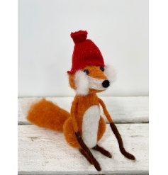 An adorable woodland fox decoration with bushy whiskers and a red knitted hat.
