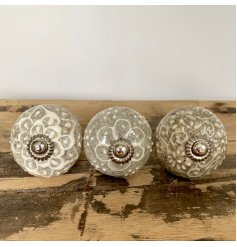 A stylish mix of ceramic doorknobs featuring intricate cream and white patterns
