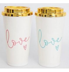 An assortment of sleek white travel mugs with added gold cap lids and scripted text decals