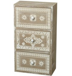 A tall standing wooden draw unit featuring an overly distressed white washed tone and beautiful decorated pattern