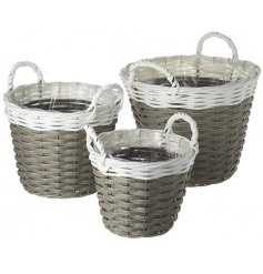 An assorted sized set of woven wicker baskets, complete with block white tones and handles