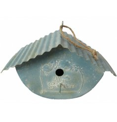A rustic metal hanging bird house complete with a rusted ribbed roof