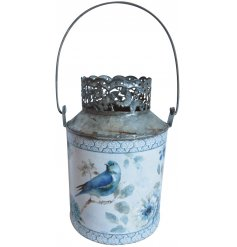 A delightfully vintage inspired metal candle holder with an added floral cut rim and blue bird decal