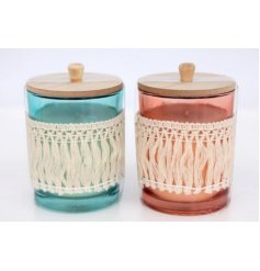 A quirky mix of pink and blue toned glass candle pots featuring natural wooden lids and a cream tassel trimming