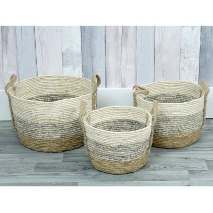A set of natural woven baskets with a subtle stripe.