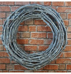 A charmingly simple round wreath built up of woven twigs in a grey tone