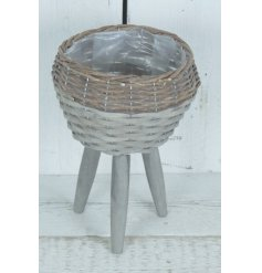 A distressed round woven wicker planter rested ontop of 3 natural wooden legs in a grey tone