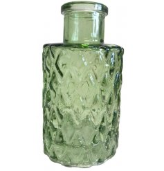 A green toned decorative bottle featuring a diamond ridged decal and small size