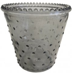 Set with a neutral grey colouring, this glass tlight holder also features a dimpled ridge effect
