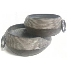 A set of 2 assorted sized metal planter bowls featuring a distressed ridged decal and added loop handles