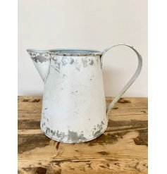 A small decorative jug with an overly distressed white tone and added vintage charm