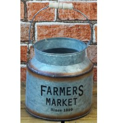A distressed zinc churn featuring a printed Farmers Market decal and rusted edging