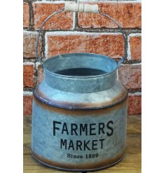 A small decorative churn featuring a bold Farmers Market printed decal and added rusted edging