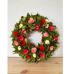 A beautiful decorated wreath with an added wooden rose feature