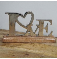 A LOVE word block featuring a silver aluminimum coating and natural wooden base