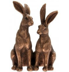 A smooth and finely finished decorative ornament of two sitting hares in a bronzed tone