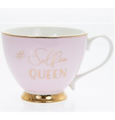 A Chic and Stylish blush pink toned mug with an added gold rim, scripted text and footed base