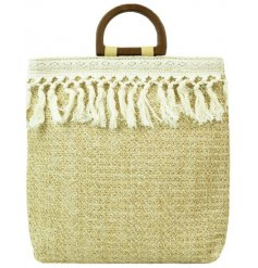 A large Woven Raffia tote bag featuring a macrame tassel trimming and wooden block handle