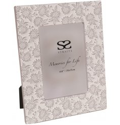 A pretty grey and white embossed photo frame with a delicate floral design. A chic gift item and interior accessory.