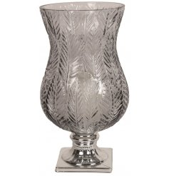 A stunning glass hurricane vase on a silver base. Complete with an embossed leaf design pattern.
