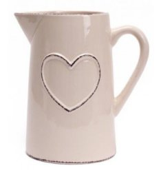 A smooth ceramic jug set with a cream tone and complete with a ridged heart decal