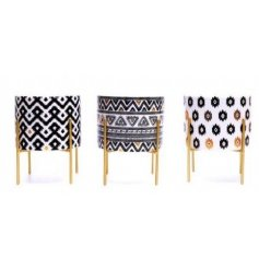 A mix of 3 Aztec inspired ceramic planters, perfectly placed ontop of gold metal legs