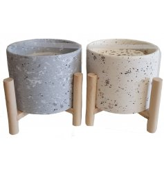 A mix of grey and mink toned Terrazzo candle pots on wooden legs
