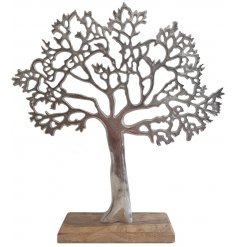 A large ornamental silvered tree decoration placed ontop a natural wooden block