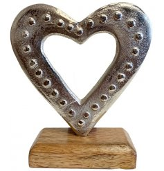 A small decorative metal heart set with a ridged beaded decal and wooden block base