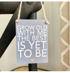 A sentimental little hanging metal sign with a scripted text quote and neutral grey base done