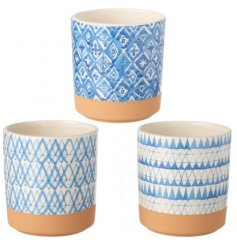 An assortment of small ceramic pots each featuring a striking blue patterned decal and terracotta toned base colour