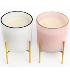 A mix of glass candle pots stood on golden toned legs