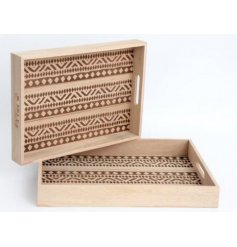 An assorted sized set of natural wooden serving trats, each featuring a beautiful African inspired trim