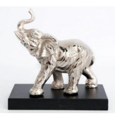 A decorative ornamental elephant set with a buffed silver tone, perfectly placed on a black wooden base