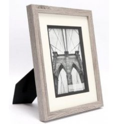 A wooden picture frame set with a grey washed tone and added chunky white boarder