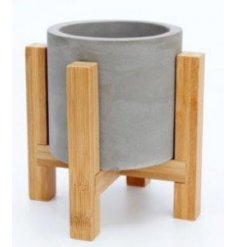 A natural grey toned concrete pot set with a smoothed edge decal and placed atop a wooden base