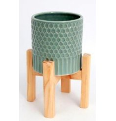 A ridged ceramic planter set with a sage green tone and placed ontop a wooden footed base