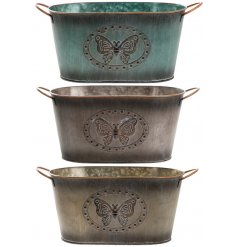 An assortment of vintage inspired metal oval planters each decorated with its own colour and embossed butterfly decal