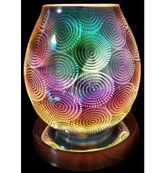 A stunning and unique glass lamp with oil burner/wax melt feature with dish, creating a multicoloured spiral image