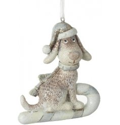 A glittery, beautifully detailed dog decoration perched upon a sleigh.