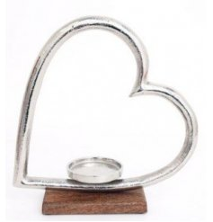 Set on top of a natural wooden block, this large silvered heart ornament also features a candle holder space