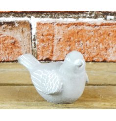 A cute little grey stone bird complete with a white washed feature