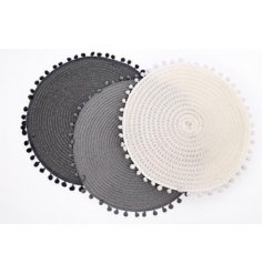 An assortment of 3 large round placemats complete with a pompom edging and trending grey and white tone