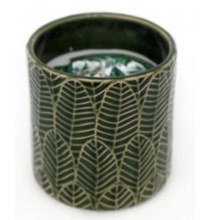 A sweetly scented candle set inside a green toned leaf pot