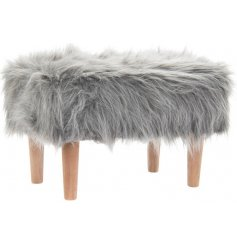 A fabulously fluffy faux fur foot stool set on top of 4 natural wooden legs