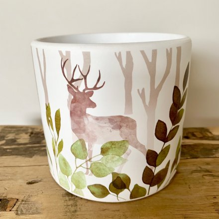 A stylish ceramic planter decorated in a colourful woodland design with stag and green foliage.