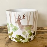 A stylish planter with a woodland design featuring colourful leaves and a stag.
