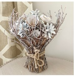 A charming white and silver bouquet bound with rustic twigs and a jute string bow.