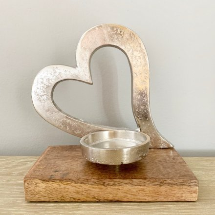 A rough luxe t-light holder set upon a chunky wooden base. Complete with a decorative tilted heart ornament.
