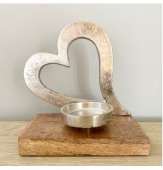 A stylish silver metal heart decoration with t-light holder, both with a textured finish set upon a chunky base.